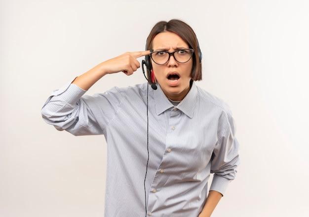 Zły młoda dziewczyna call center w okularach i zestaw słuchawkowy kładąc palec na świątyni na białym tle na biały z miejsca na kopię