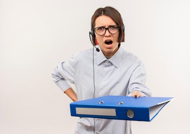 Zły młoda dziewczyna call center w okularach i zestaw słuchawkowy wyciągając schowek kładąc rękę na talii na białym tle na biały z miejsca na kopię