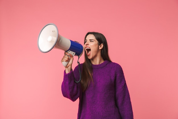 Zły młoda dziewczyna ubrana w sweter stojący na białym tle nad różowym, krzycząc w głośniku