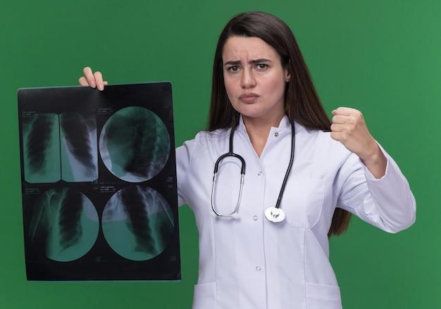 Zły młoda kobieta lekarz ubrana w szlafrok medyczny ze stetoskopem trzyma pięść i trzyma wynik prześwietlenia na zielono