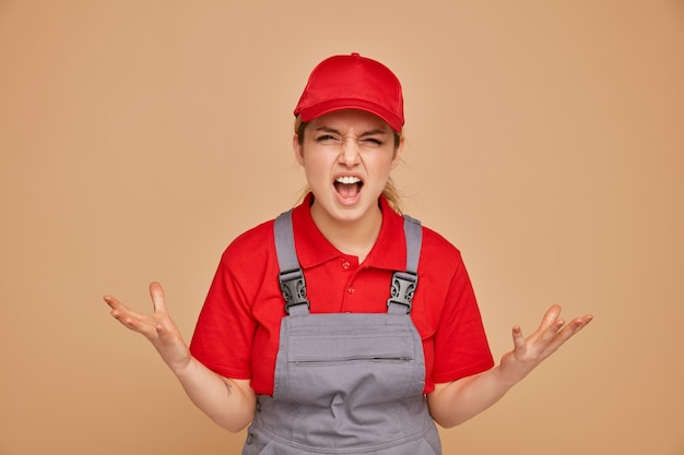 Zły młoda kobieta pracownik budowlany na sobie mundur i czapkę krzycząc pokazując puste ręce