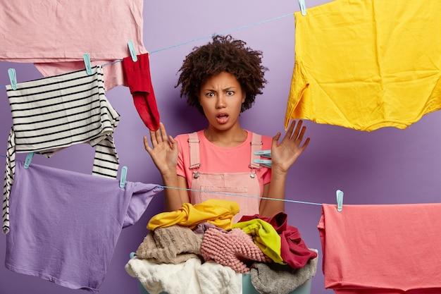 Zły młoda kobieta z afro pozowanie z praniem w kombinezonie