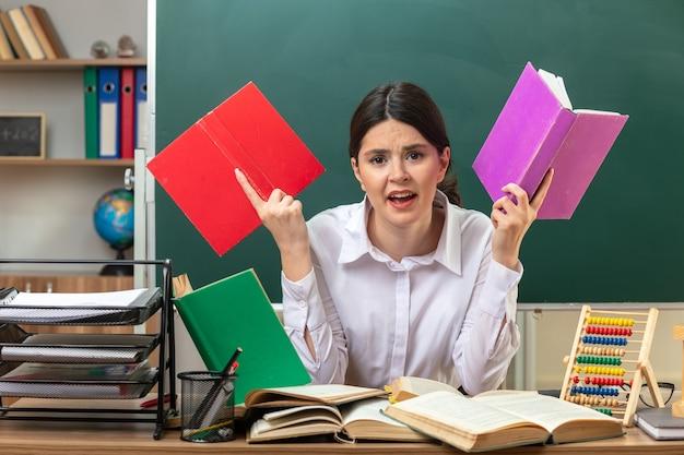 Zły młoda nauczycielka trzyma książkę siedzącą przy stole z narzędziami szkolnymi w klasie