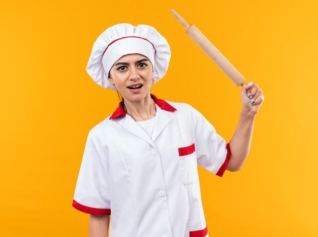 Zły młoda piękna dziewczyna w mundurze szefa kuchni trzymając wałek do ciasta