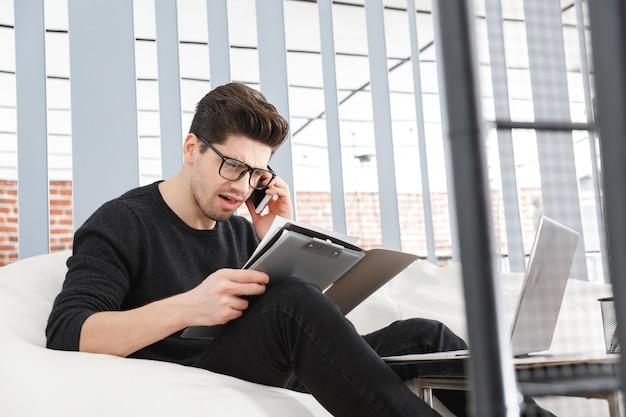 Zły młody biznesmen pracuje w biurze siedząc na kanapie, rozmawiając przez telefon komórkowy