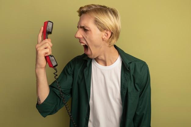 Zły młody blondyn na sobie zieloną koszulkę, trzymając i patrząc na telefon