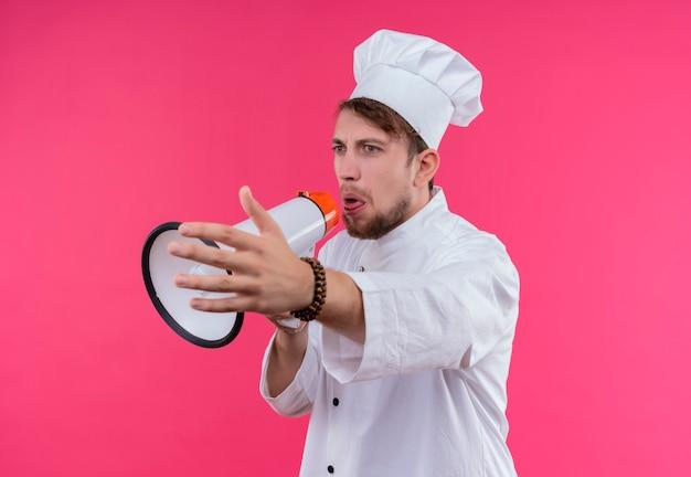 Zły młody, brodaty szef kuchni w białym mundurze wyciąga rękę podczas mówienia przez megafon na różowej ścianie