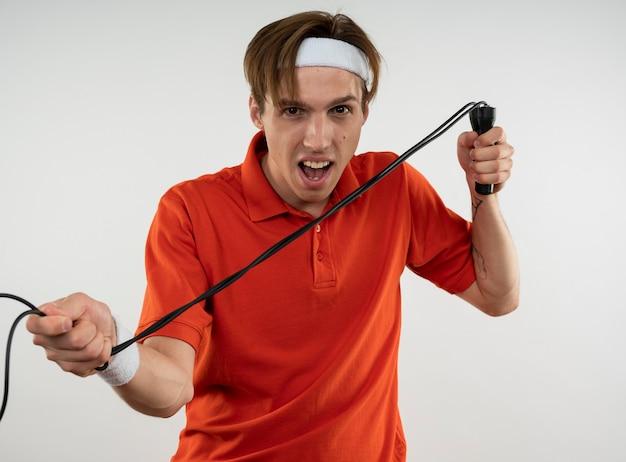 Zły młody chłopak sportowy sobie opaskę z nadgarstkiem rozciąganie skakanka na białym tle na białej ścianie