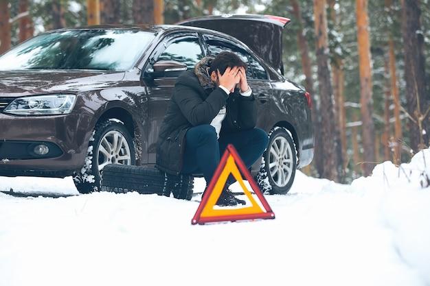 Zły młody człowiek czeka na pomoc, siedząc zimą w lesie w pobliżu zepsutego samochodu na poboczu drogi