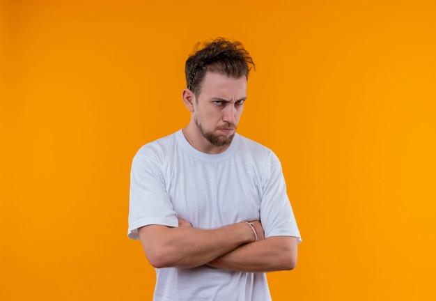 Zły młody człowiek ubrany w białą koszulkę skrzyżowaniu rąk na na białym tle pomarańczowa ściana