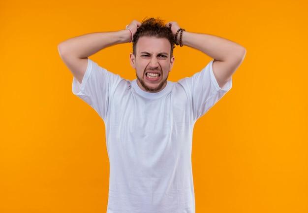 Zły młody człowiek ubrany w białą koszulkę złapał głowę na odizolowanej pomarańczowej ścianie