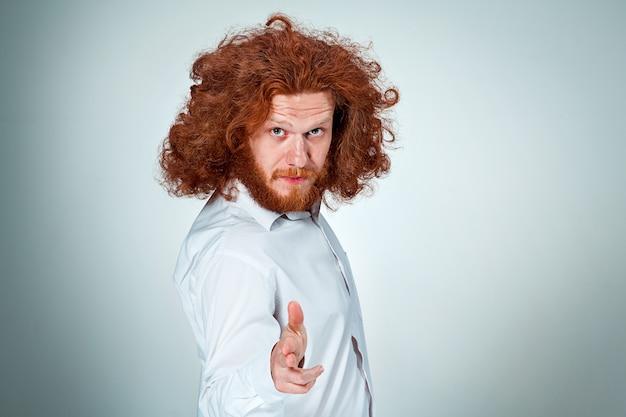 Zły młody człowiek z długimi rudymi włosami, mając cel w aparacie
