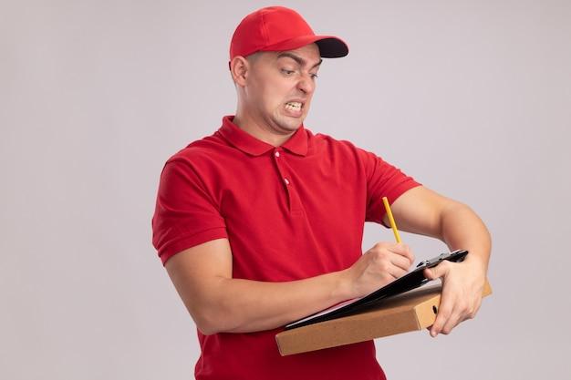 Zły młody dostawa człowiek ubrany w mundur z czapką trzyma pudełko po pizzy i pisze coś w schowku na białym tle na białej ścianie