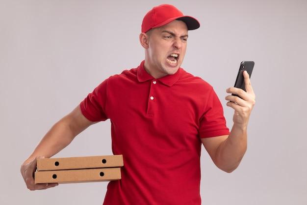 Zły młody dostawa człowiek ubrany w mundur z czapką, trzymając pudełka po pizzy i patrząc na telefon w ręku na białym tle na białej ścianie