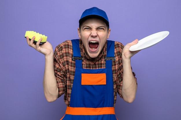 Zły młody facet sprzątający ubrany w mundur i czapkę trzymającą talerz z gąbką