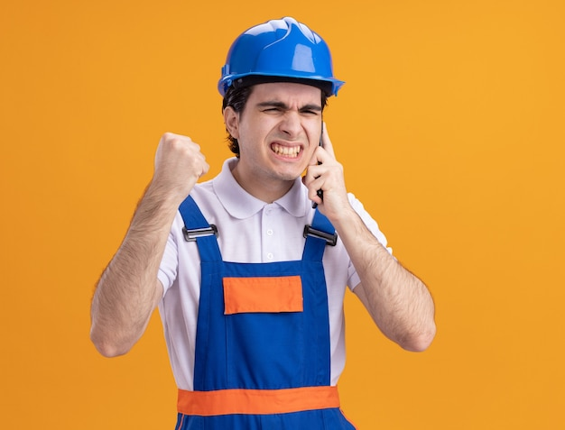 Zły młody konstruktor w mundurze budowy i hełmie ochronnym rozmawia przez telefon komórkowy stojący nad pomarańczową ścianą