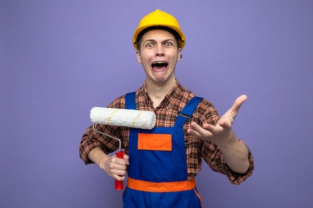 Zły młody mężczyzna budowniczy ubrany w mundur trzymający szczotkę rolkową