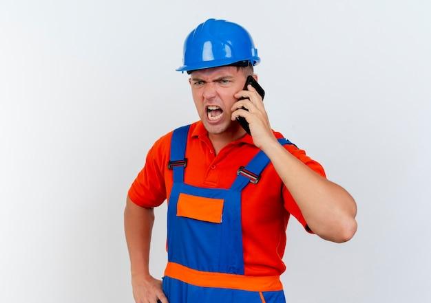 Zły młody mężczyzna budowniczy w mundurze i hełmie ochronnym mówi przez telefon
