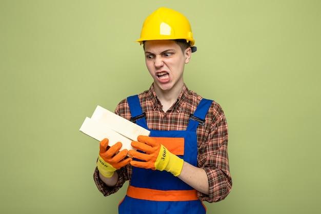 Zły młody mężczyzna budowniczy w mundurze w rękawiczkach, trzymający i patrzący na cegły
