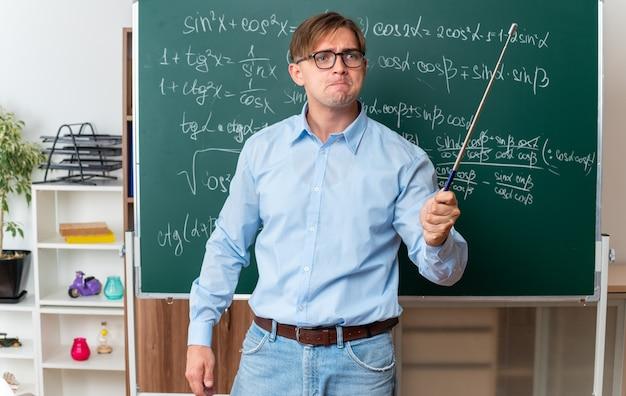Zły młody nauczyciel płci męskiej w okularach ze wskaźnikiem wyjaśniającym lekcję stojącą przy tablicy z formułami matematycznymi w klasie