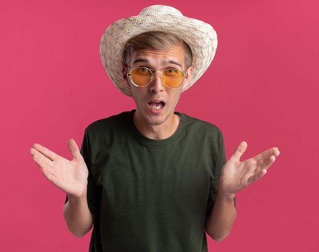 Zły młody przystojny facet na sobie zieloną koszulę i okulary z kapeluszem, rozkładając ręce na białym tle na różowej ścianie