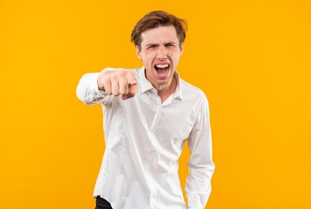 Zły młody przystojny facet ubrany w białą koszulę pokazujący gest odizolowany na pomarańczowej ścianie
