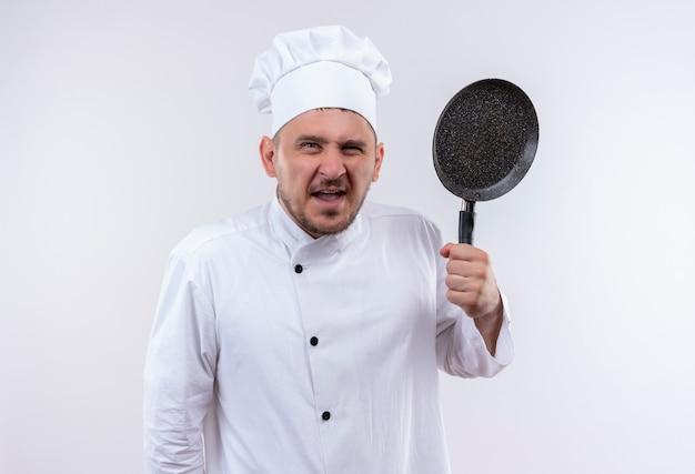 Zły młody przystojny kucharz w mundurze szefa kuchni, trzymając patelnię na białym tle na białej ścianie