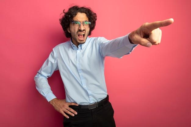 Zły młody przystojny mężczyzna w okularach, trzymając rękę na talii, patrząc i wskazując na bok na białym tle na różowej ścianie