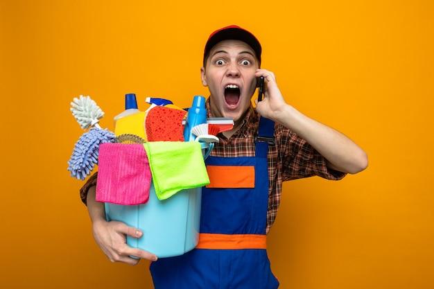 Zły młody sprzątacz ubrany w mundur i czapkę trzymającą wiadro z narzędziami do czyszczenia mówi przez telefon