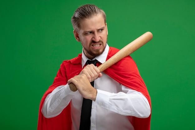 Zły młody superbohater facet i umieszczenie nietoperza basebale na ramieniu odizolowane na zielono