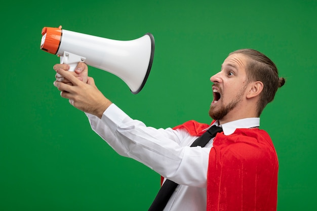 Zły młody superbohater facet sobie krawat patrząc z boku i trzymając głośnik z boku na białym tle na zielonym tle