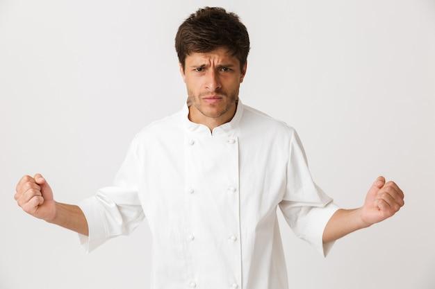 Zły młody szef kuchni człowiek stojący na białym tle na białej ścianie.