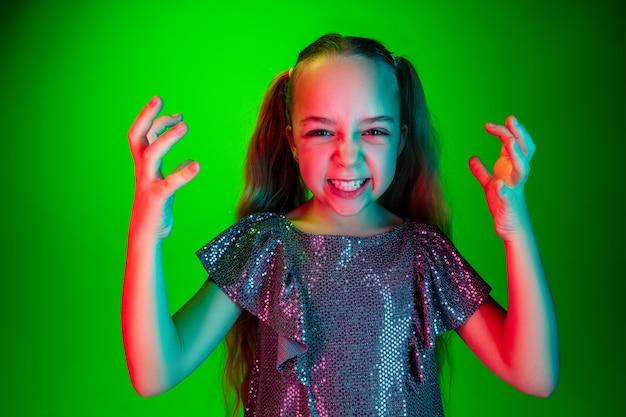 Zły nastolatek dziewczyny stojącej na modnej zieleni
