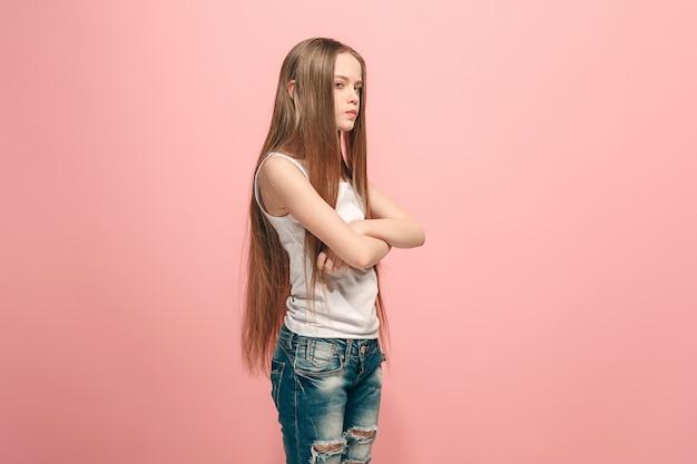 Zły nastolatek dziewczyny stojącej na modnym różu. portret kobiety w połowie długości