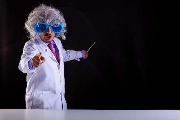 Zły nauczyciel przyrody w białym fartuchu z rozczochranymi włosami w śmiesznych okularach wskazuje palcem na czarnym tle
