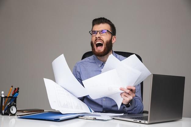 Zły niezadowolony brodaty elegancki mężczyzna w okularach trzymający dokumenty siedząc przy stole w biurze