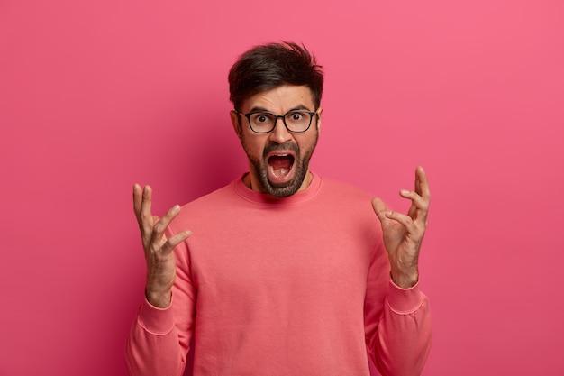 Zły oburzony mężczyzna gestykuluje gniewnie i głośno krzyczy