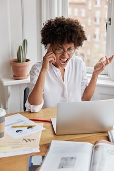Zły oburzony młoda bizneswoman pracuje w domu