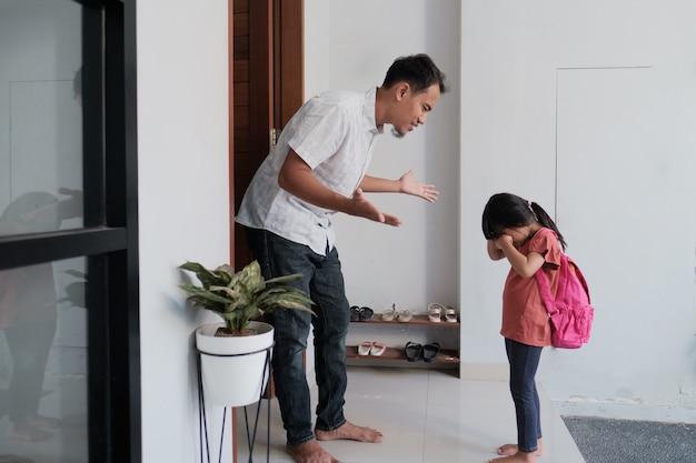 Zły ojciec rozmawia z dzieckiem po szkole. azjatycki problem z podstawowymi uczniami. agresywny rodzic z córką