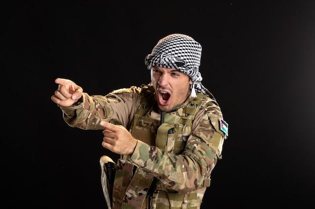 Zły palestyński żołnierz w wojskowym mundurze na czarnej ścianie