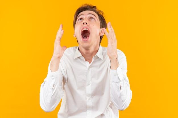 Zły patrząc w górę młody przystojny facet ubrany w białą koszulę odizolowaną na pomarańczowej ścianie