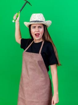 Zły piękny ogrodnik dziewczyna w mundurze na sobie kapelusz ogrodniczy podnoszący motyka grabie na białym tle na zielonym tle