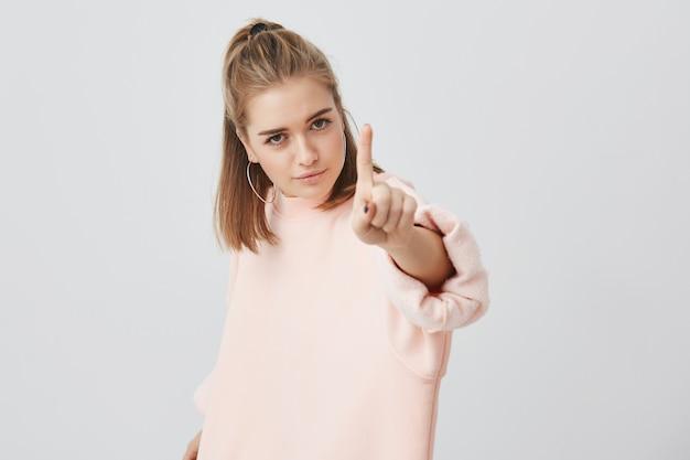 Zły poważna dziewczyna z apelacją patrzy, trzymając palec wskazujący przed sobą, mówiąc: hej, poczekaj chwilę. ufna młoda europejska kobieta broni swojej pozycji i poglądów. język ciała.