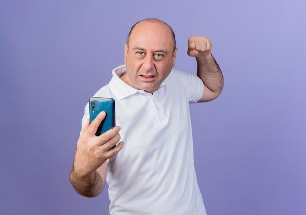Zły przypadkowy dojrzały biznesmen trzymając telefon komórkowy i podnosząc pięść, przygotowując się do kopnięcia na białym tle na fioletowym tle z miejsca na kopię