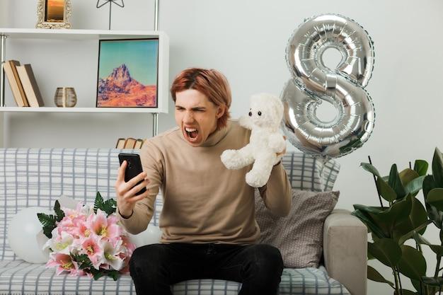 Zły przystojny facet na szczęśliwy dzień kobiet trzymający pluszowego misia patrzącego na telefon w ręku, siedzącego na kanapie w salonie