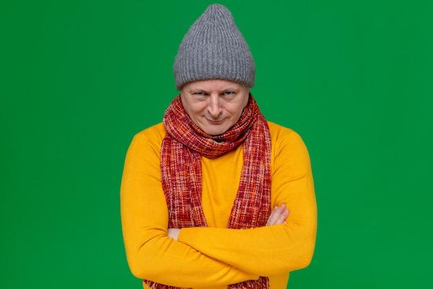 Zły radosny dorosły słowiański mężczyzna w zimowej czapce i szaliku na szyi stojący ze skrzyżowanymi rękami i