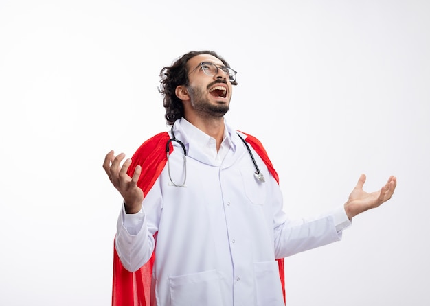 Zły radosny młody kaukaski mężczyzna superbohatera w okularach optycznych w mundurze lekarza z czerwonym płaszczem i stetoskopem na szyi trzyma ręce otwarte i patrzy w górę na białym tle na białej ścianie