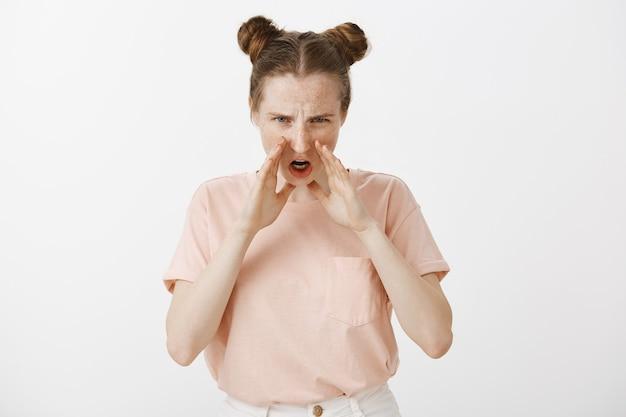 Zły, rozczarowany, ruda nastolatka pozuje na białej ścianie