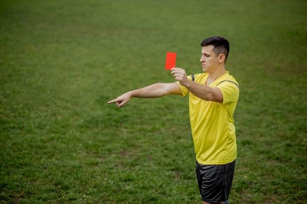 Zły sędzia piłkarski pokazujący czerwoną kartkę i wskazujący ręką na karę.