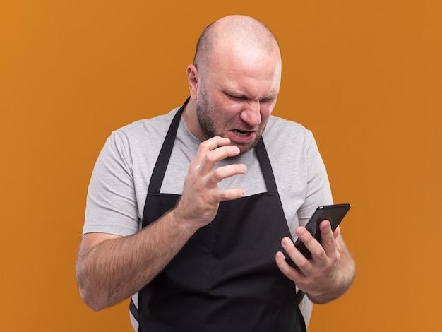 Zły słowiański mężczyzna w średnim wieku fryzjer w mundurze, trzymając i patrząc na telefon na białym tle na pomarańczowej ścianie